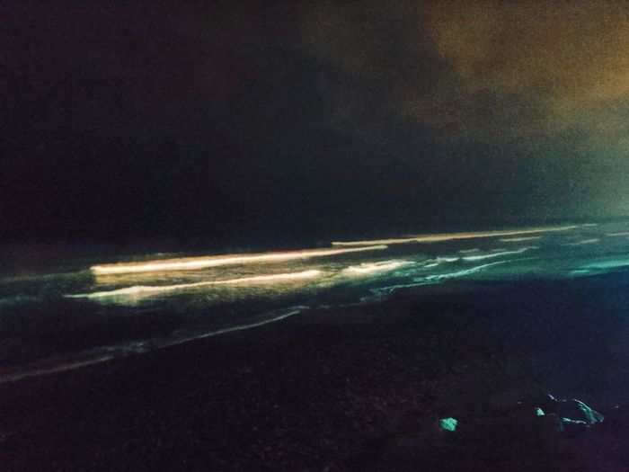 Aerial view of illuminated sea against sky at night