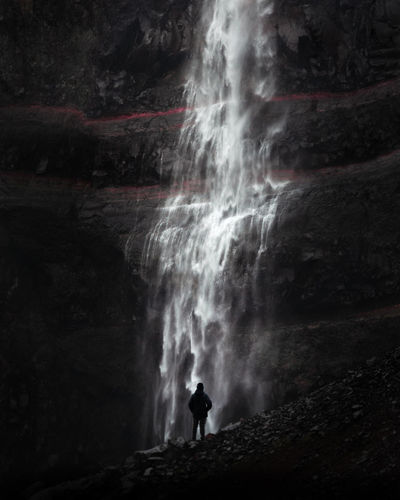 Silhouette man looking at waterfall on mountain