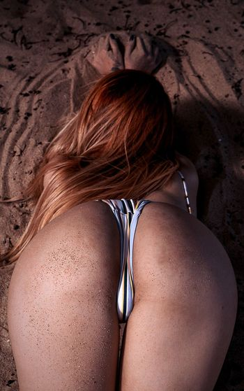 Rear View Of Seductive Woman Lying On Sand
