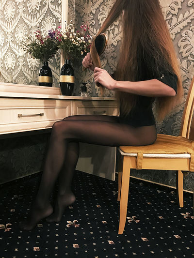 Side view of seductive woman combing hair while sitting on chair at home