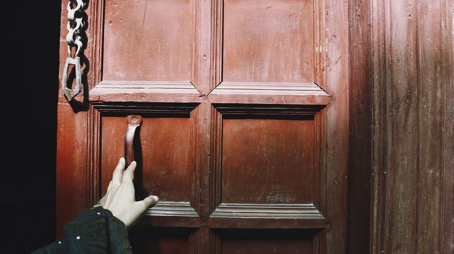 Historic wooden door and a female hand
