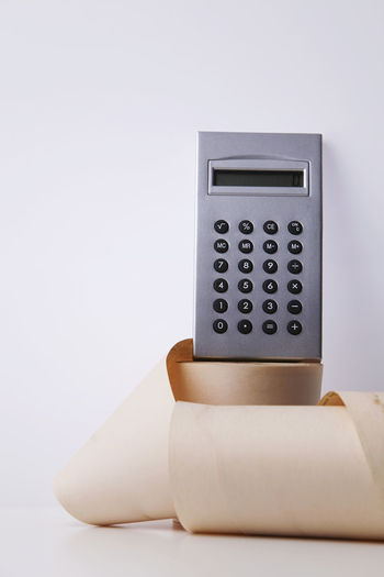 Close-up of calculator and paper roll on table against white background