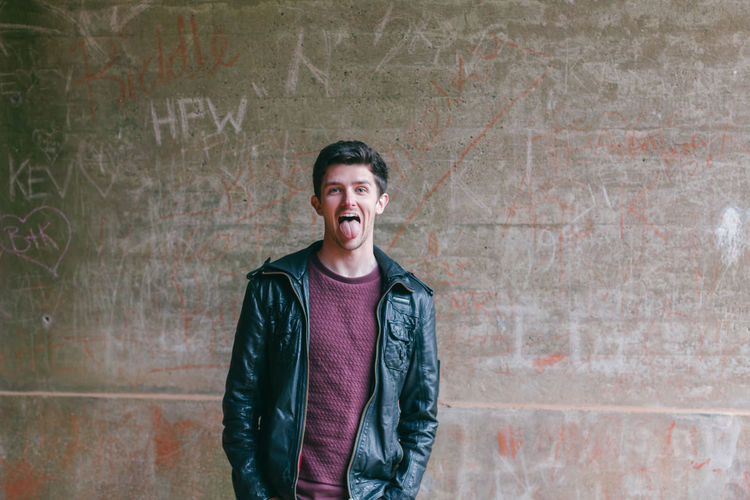 Portrait of young man in leather jacket sticking out tongue against wall