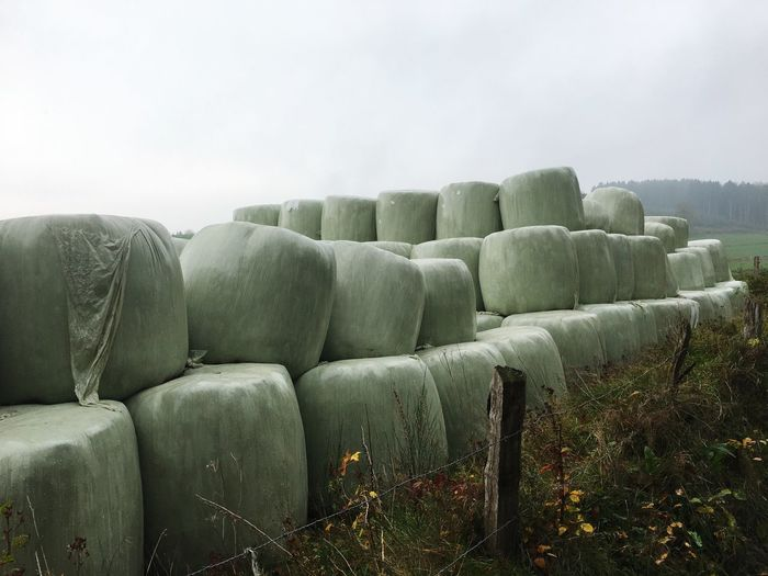 Stack of hay bales on field against sky