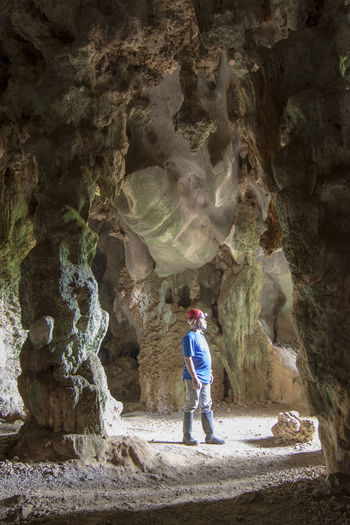 Full length of man standing on rock in cave