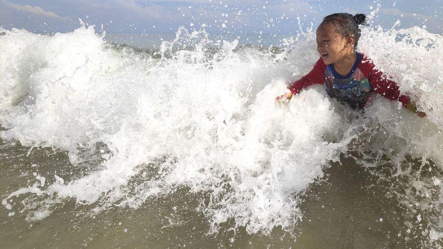 Full length of a boy splashing water