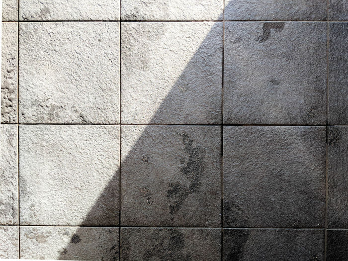 full frame shot of tiled floor Architecture Backgrounds Built Structure Close-up Concrete Day Design Flooring Full Frame Gray Nature No People Outdoors Pattern Paving Stone Shadow Solid Stone Wall Sunlight Textured  Tile Tiled Floor Wall Wall - Building Feature