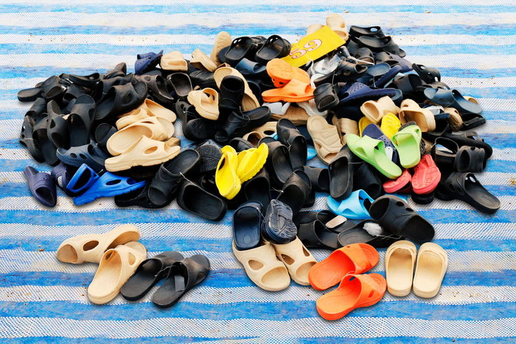 High angle view of multi colored flip flops on striped textile