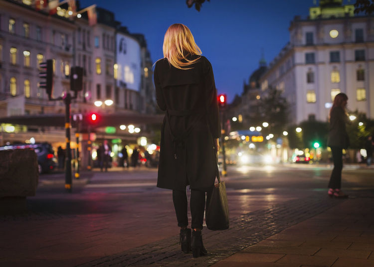 Rear view of woman standing on city street at night