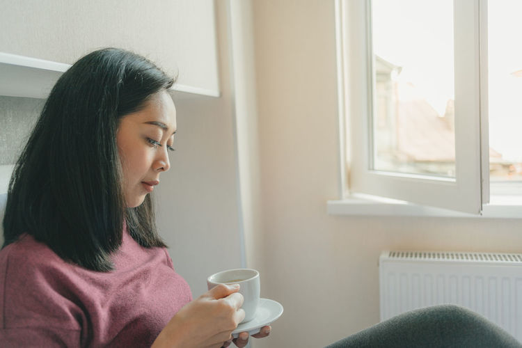Young woman drinking coffee cup at home