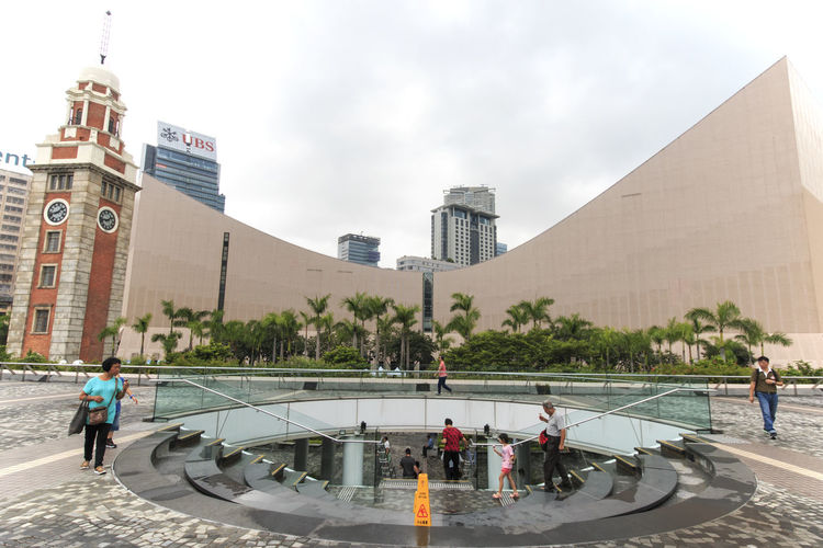 People by clock tower at tsim sha tsui by sea in city