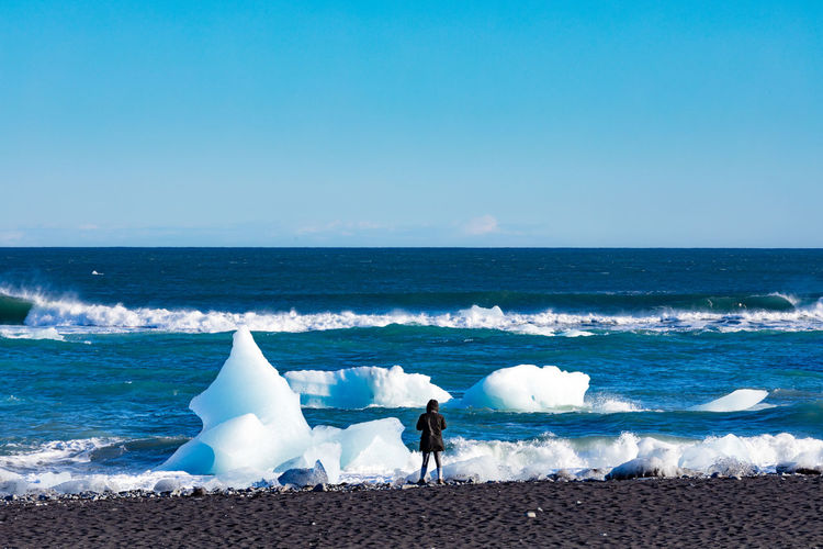 Person on black sand Diamond Beach watching glacier ice in Atlantis Ocean surf washed ashore from glacier lagoon of Jokulsarlon, Iceland, IS, Europe Diamond Beach Diamond Beach Iceland Diamond Beach, Iceland,Jokulsarlon, Jökulsárlón Glacial Glacier Ice Iceberg Melting Melt Melting Ice Beach Atlantic Ocean, Surf Sea Iceland Europe Travel Destination person Watching Observing Tourist Exploring Ashore Water Horizon Over Water Wave Beauty In Nature Scenics - Nature Nature Outdoors Horizon Leisure Activity The Great Outdoors - 2019 EyeEm Awards