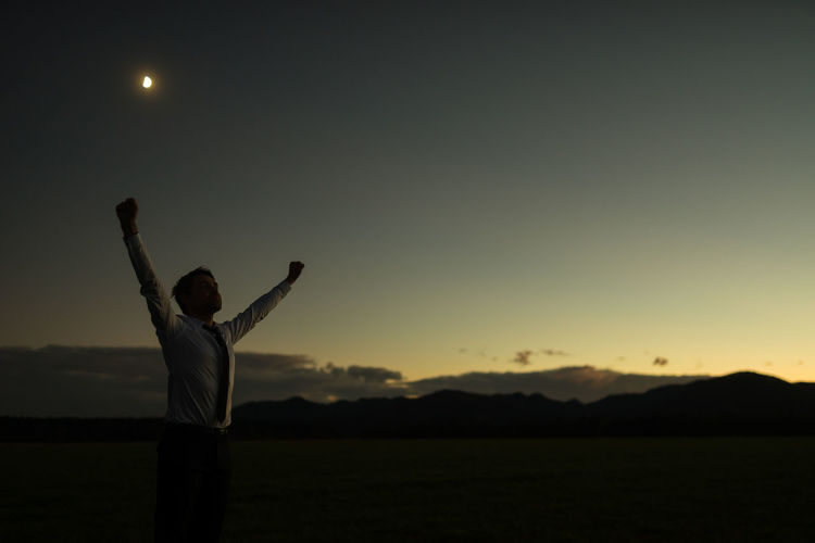 Man with arms raised standing on land against sky during sunset