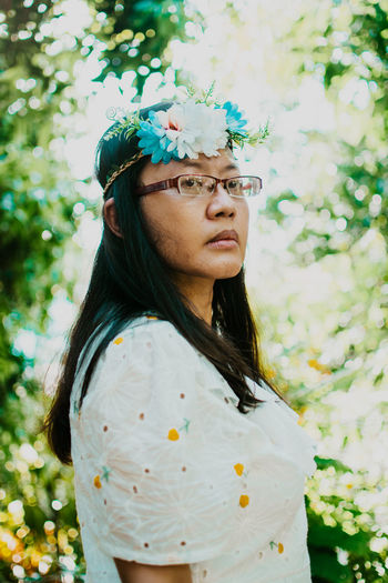 Portrait of a beautiful young woman standing by flowering plants
