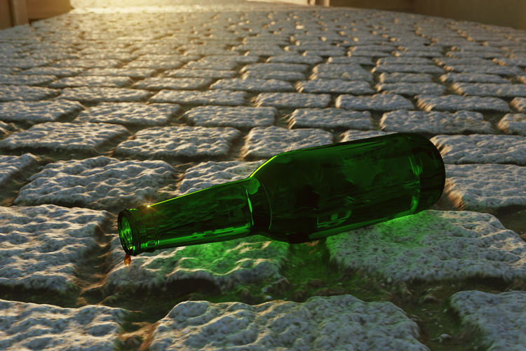 green empty beer bottle with the last drop of alcohol laying on cobblestone street Beer Bottle Beer Alcohol Alcoholism Cobblestone Laying Drop Last Close-up Addiction Quit Stone Sunlight Green Color Street Liquid Empty Green Drunkard Drunk Symbol Despair