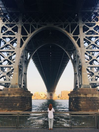 Rear view of woman standing on bridge