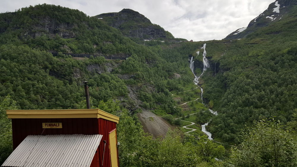 The Flåm Line (Norwegian: Flåmsbana) is a 20.2-kilometer (12.6 mi) long railway line between Myrdal and Flåm in Aurland, Norway. A branch line of the Bergen Line, it runs through the valley of Flåmsdalen and connects the mainline with Sognefjord. The line's elevation difference is 863 meters (2,831 ft); it has ten stations, twenty tunnels and one bridge. The maximum gradient is 5.5 percent (1:18). Because of its steep gradient and picturesque nature, the Flåm Line is now almost exclusively a tourist service and has become the third-most visited tourist attraction in Norway. Construction of the line started in 1924, with the line opening in 1940. It allowed the district of Sogn access to Bergen and Oslo via the Bergen Line. Electric traction was taken into use in 1944; at first El 9 locomotives were used, and from 1982 El 11. Until 1991, the train connected with a ferry service from Flåm to Gudvangen. In 1992, freight services were terminated, and due to low ticket prices and high operating costs, the line was nearly closed. In 1998, Flåm Utvikling took over marketing and ticket sale for the line, prices were heavily increased and El 17 locomotives were introduced. The trains remain operated by the Norwegian State Railways (NSB), while the line itself is owned and operated by the Norwegian National Rail Administration. Aurland EyeEm Nature Lover Flamsbana Flåm Flåm Line Hidden Gems  Historic Mountain Mountains Myrdal Nature Nature Photography Nature_collection Naturelovers Naturephotography Nsb Railway River Scandinavia The Purist (no Edit, No Filter) Tourism Touristic Train Waterfall Waterfalls
