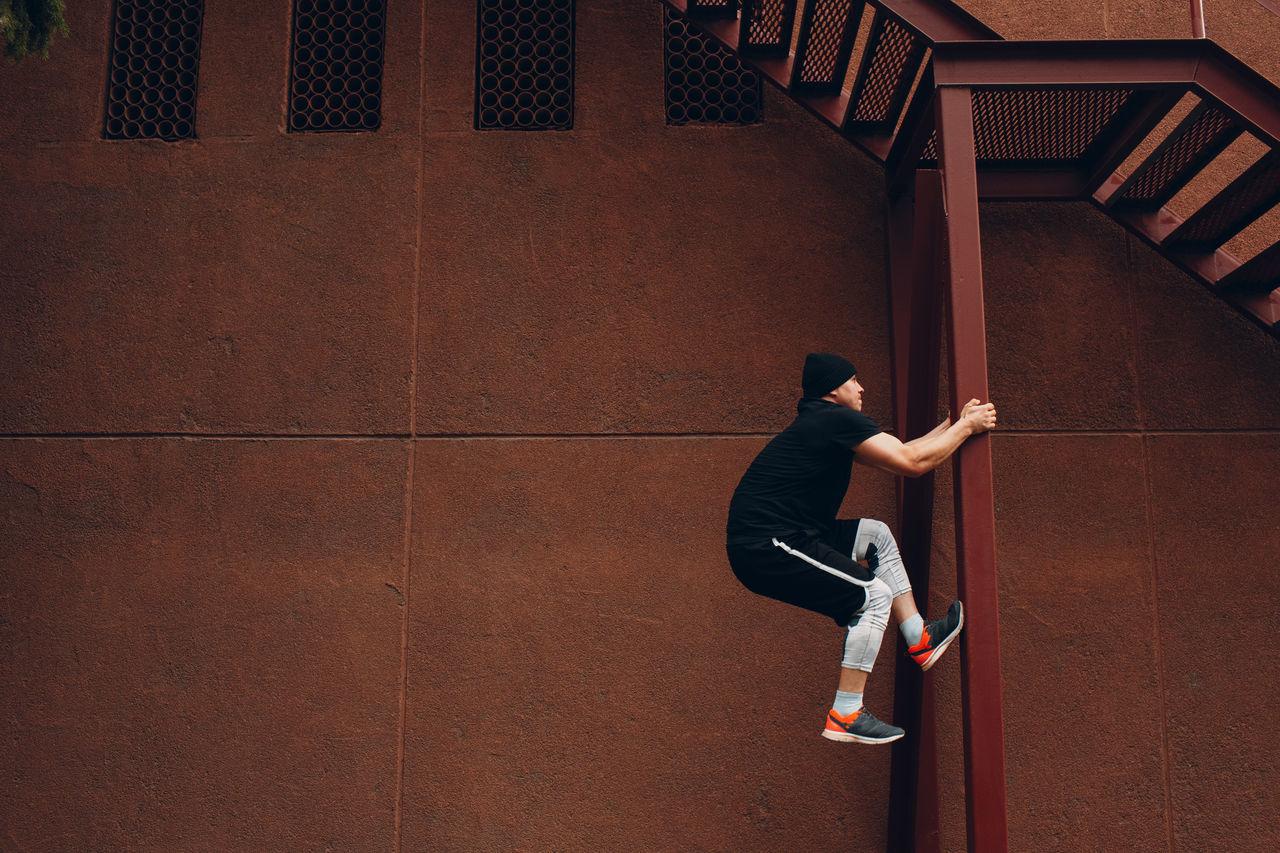 Man climbing on metal column against brown wall