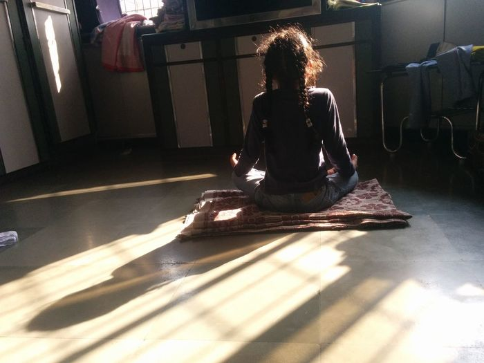 Rear view of girl doing yoga on floor at home