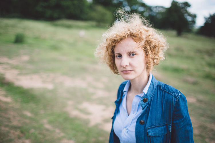 Beautiful Woman Blond Hair Casual Clothing Curly Hair Day Field Focus On Foreground Leisure Activity Lifestyles Looking At Camera Medium-length Hair Nature One Person Outdoors Portrait Real People Richmond Park, London Standing Young Adult Young Women The Portraitist - 2017 EyeEm Awards