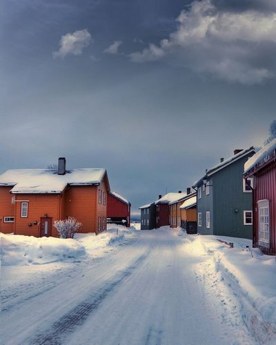 Frozen houses against sky during winter