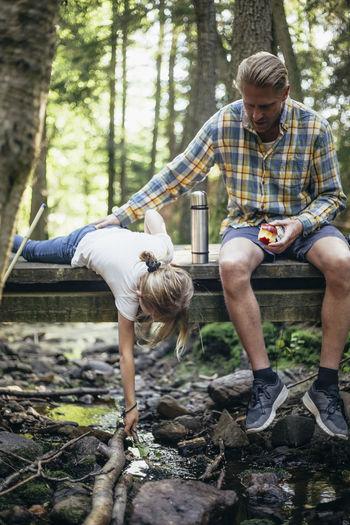 Full length of men sitting in forest