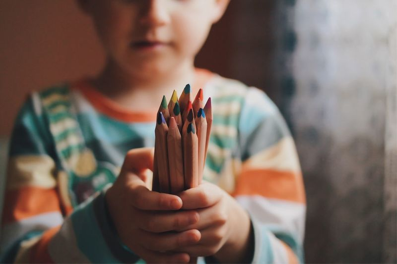 Midsection Of Boy Holding Colored Pencils At Home