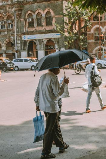 Rear view of men walking on street in city