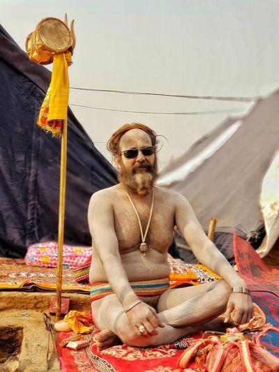 Full length of naked sadhu sitting outdoors
