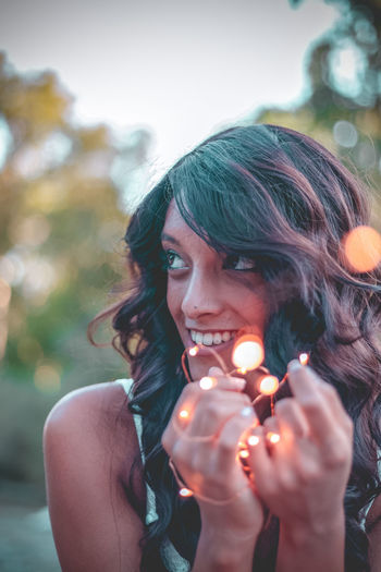 Smiling Young Woman Holding Illuminated Lighting Equipment While Sitting Against Sky