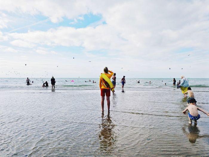 People enjoying on beach against sky