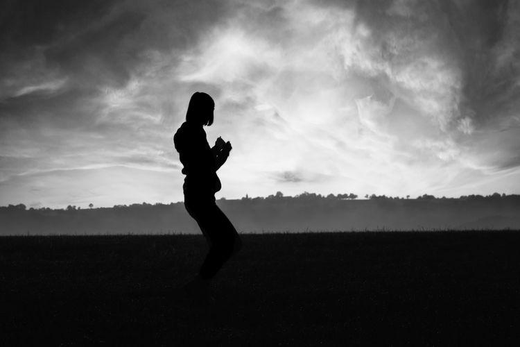 Silhouette women standing on field against sky