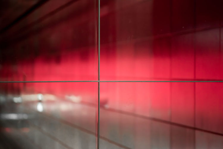 Full frame shot of tiled red reflecting metal wall