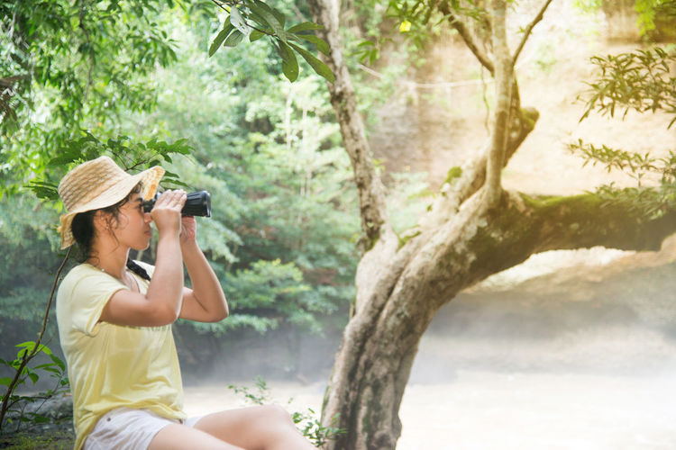 Young Woman Looking Thorough Binoculars In Forest