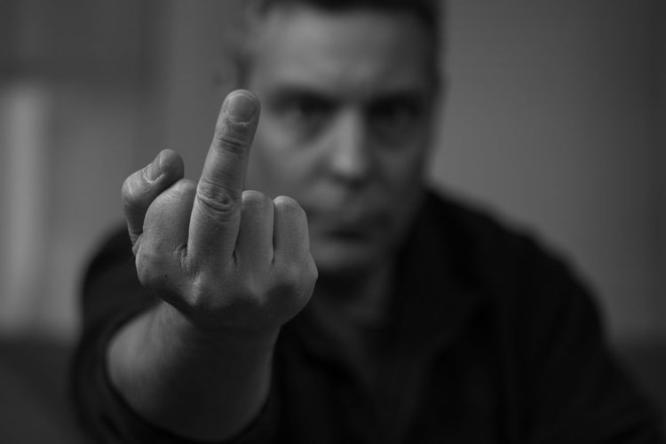 Portrait of rude man showing middle finger