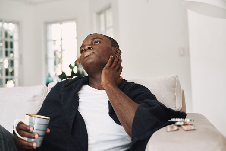 Tired man looking away while sitting with coffee cup on sofa at home