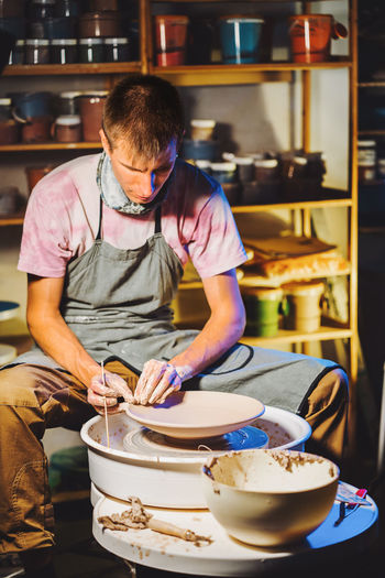Potter making pot while sitting in pottery workshop