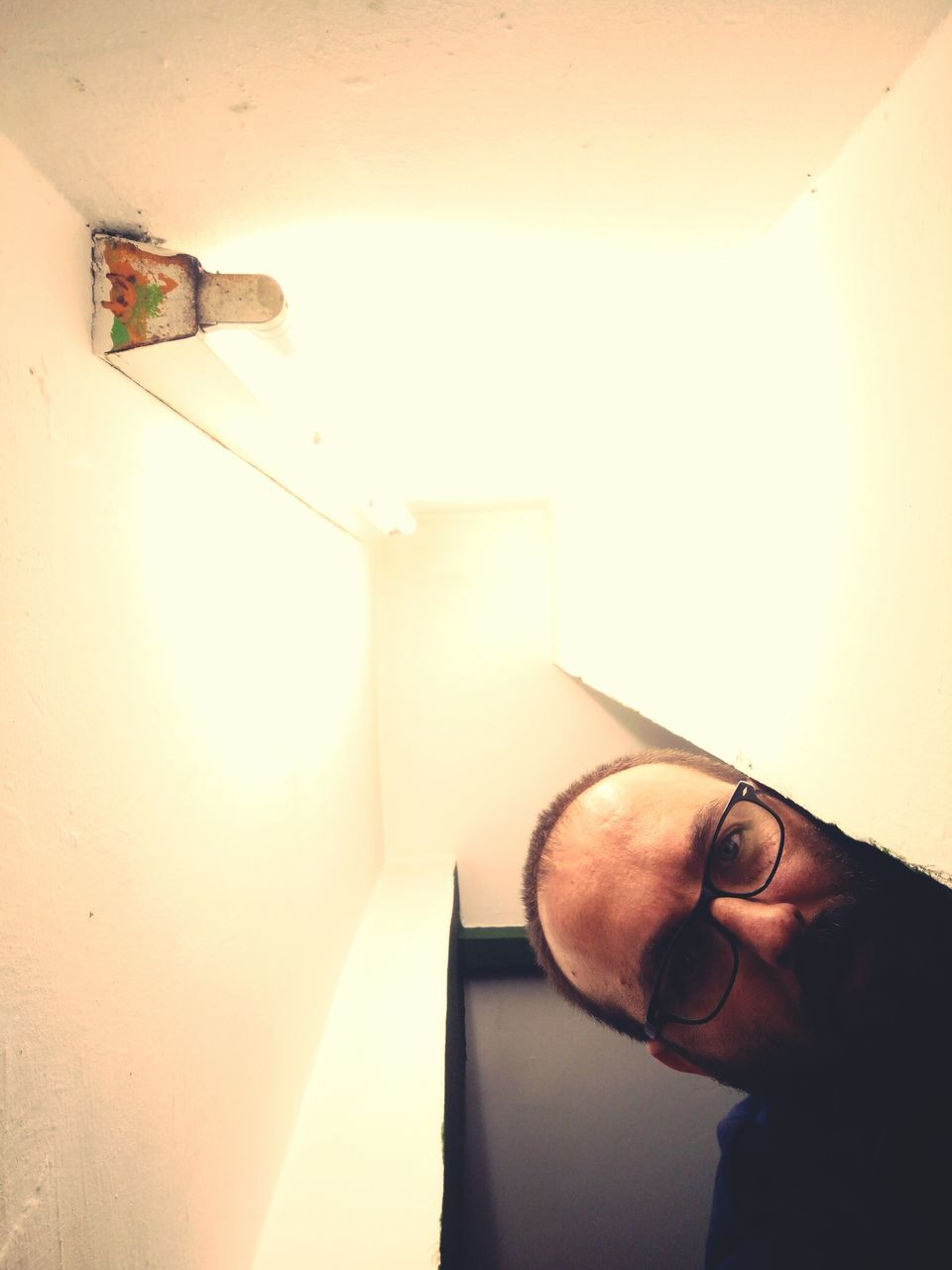 Portrait Of Man By Illuminated Florescent Light Against Ceiling