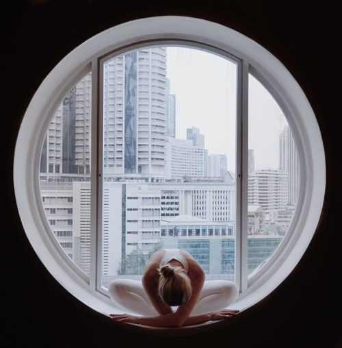 Full Length Of Woman Practicing Yoga At Circular Window