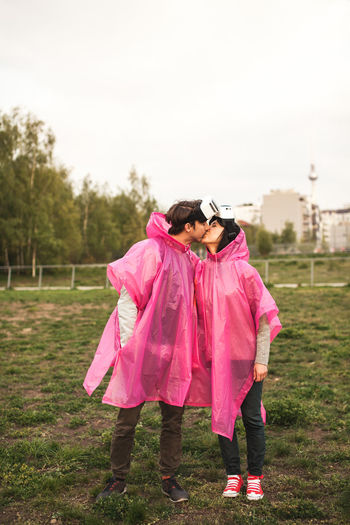 Young couple wearing raincoat and virtual reality simulator while kissing at park
