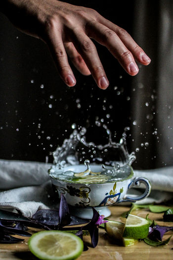 Hand above splashing cup of water