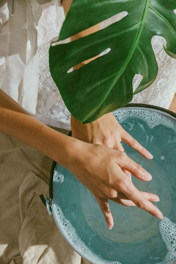 Midsection of woman cleaning hands in water