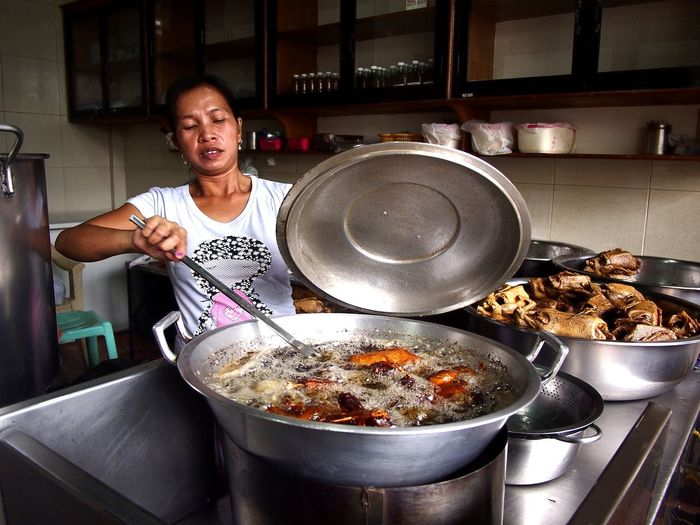 Asian woman deep frying ducks in her restaurant's kitchen Meal Breakfast Lunch Dinner Viand Human Hand Asian  Filipino Asianfood Filipino Food Deep Fried  Duck Fried Duck Fried Itik Dish Cuisine Stove Kitchen Preparation  Healthy Lifestyle Domestic Kitchen Food And Drink Frying Pan Prepared Food Cooking Pan Pan Boiling Gas Stove Burner Burner - Stove Top Cooking Utensil Fried Food