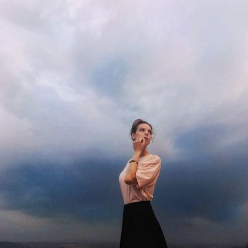 Low angle view of thoughtful young woman while standing against cloudy sky
