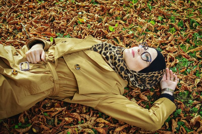 High Angle View Of Woman Lying Down On Fallen Dry Leaves