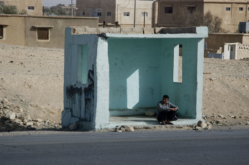 man waiting at a bus stop at the side of the road, Jordan Jordan Middle East Road Travel Architecture Building Exterior Built Structure Bus Busstop Commute Day Full Length Lifestyles Men Middleofnowhere One Person Outdoor Photography Outdoors People Real People Sitting Terminal Young Adult The Week On EyeEm