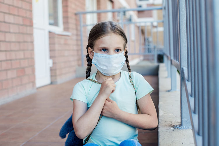 Close-up of cute girl wearing mask standing by building