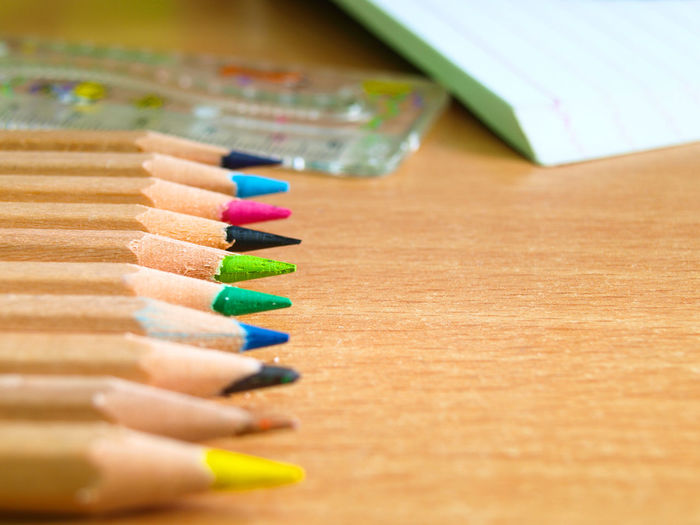Close-up of multi colored pencils and ruler on wooden table