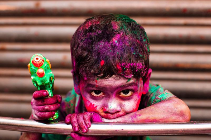 Portrait of boy covered with colors holding holi gun