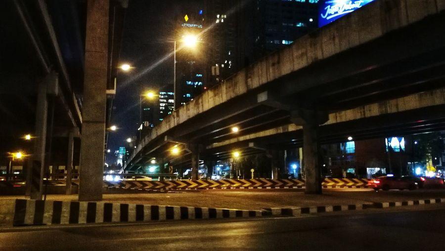 Illuminated bridge over street in city at night